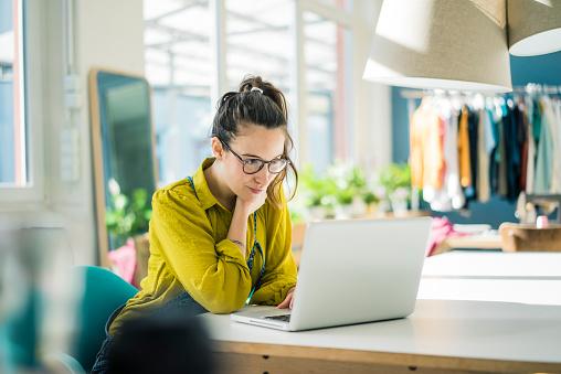 Fashion designer sitting at desk in her studio looking at laptop - gettyimageskorea