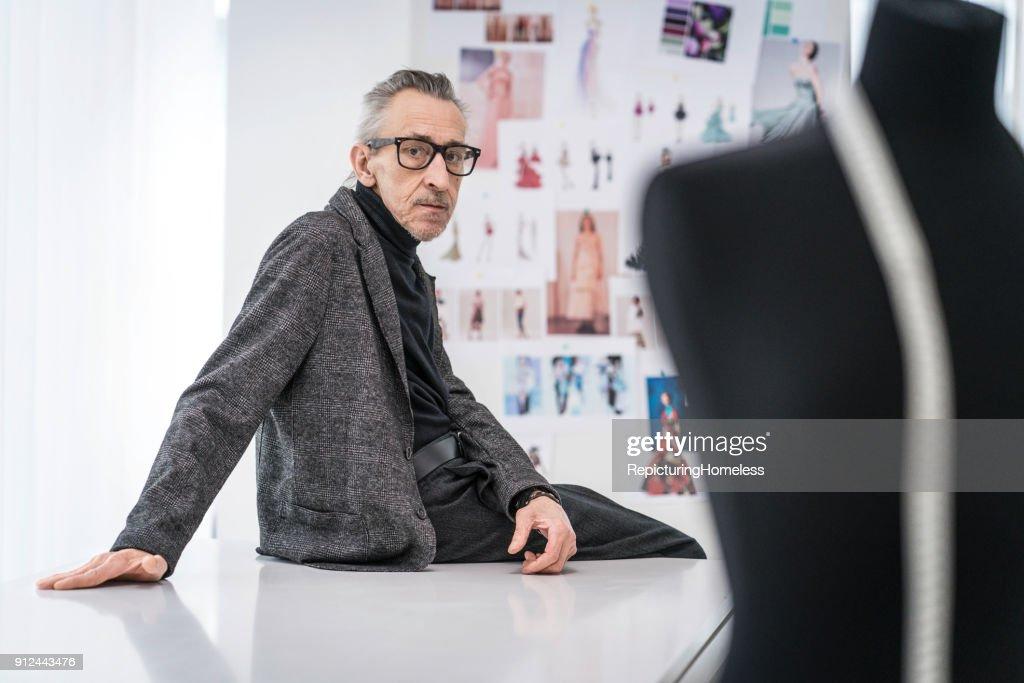 Mode-Designer sitzt auf einem Tisch : Stock-Foto