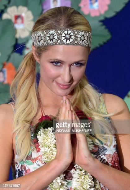 Fashion designer socialite and DJ Paris Whitney Hilton folds her hands in a namaste traditional Indian greeting during a visit to an orphanage in...