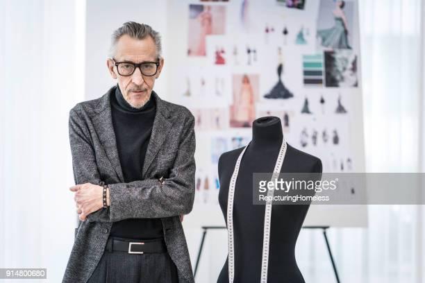 Mode-Designer steht in seinem Atelier und schaut in die Kamera