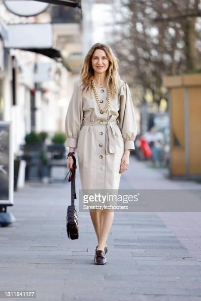 Fashion designer Sue Giers wearing a beige trench dress by SoSUE, a dark brown bag by Bottega Veneta, dark brown shoes by Bottega Veneta and a gold...