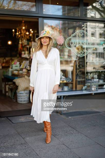 Fashion designer Sue Giers wearing brown knee high boots by Celine, a long white longsleeve dress by SoSUE, a multicolor floral print hat by...