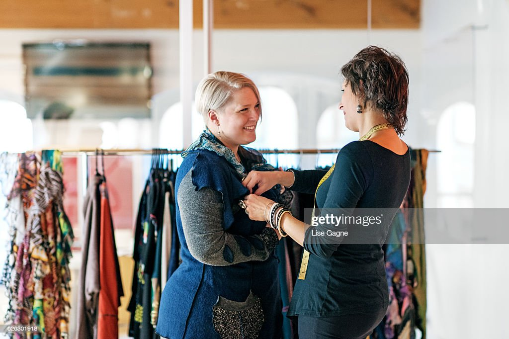 Fashion designer  taking customer measurement in clothing boutique : Foto de stock