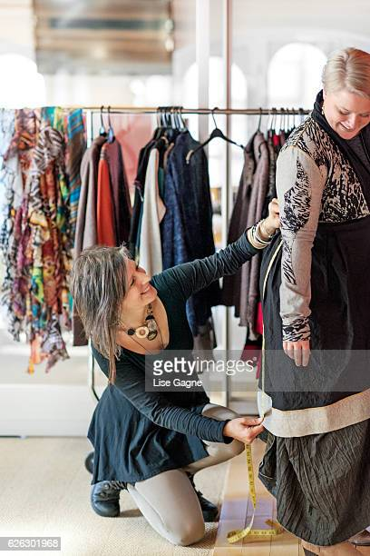 Fashion designer  taking customer measurement in clothing boutique