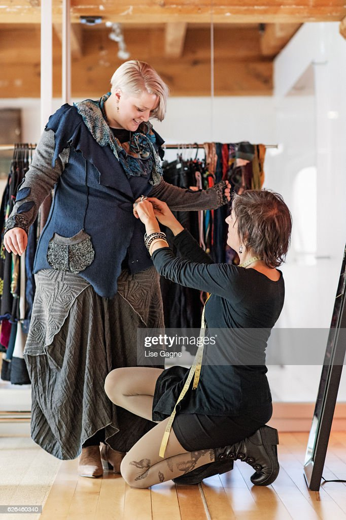 Fashion designer  taking customer measurement in clothing boutique : Stock-Foto