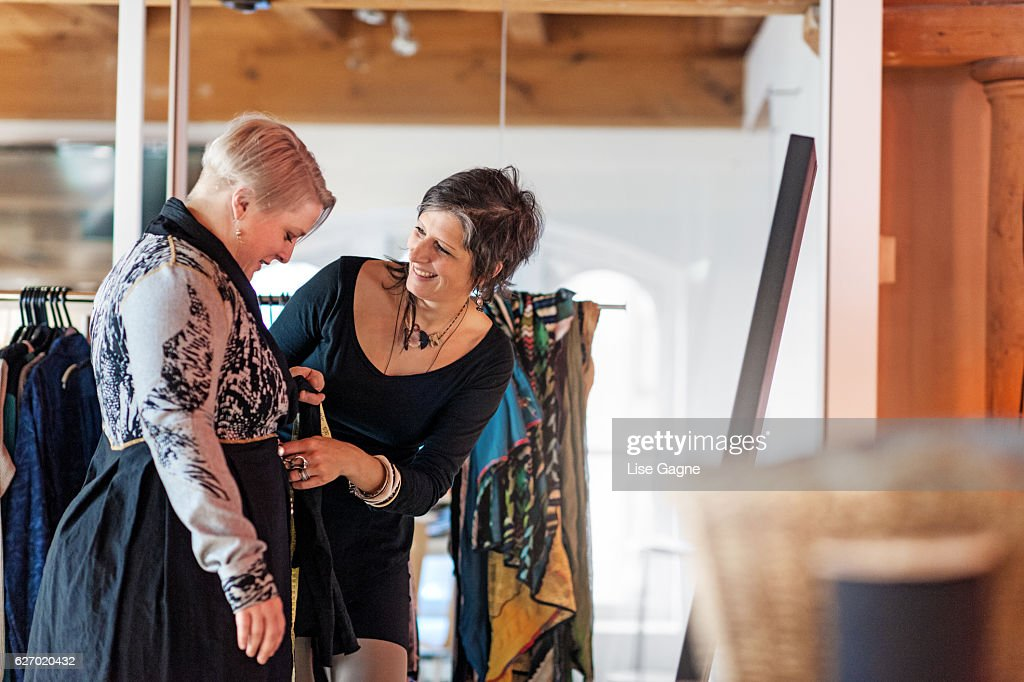 Fashion designer  taking customer measurement in clothing boutique : Stock Photo