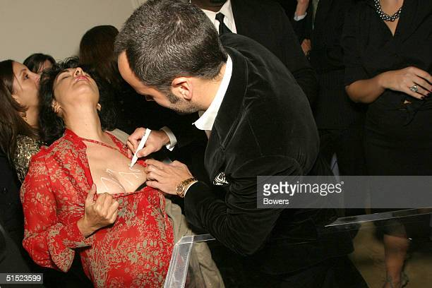 Fashion designer Tom Ford signs Tracey Moffatt at the book launch party for 'Tom Ford:Ten Years' at Bergdorf Goodman October 20, 2004 in New York...