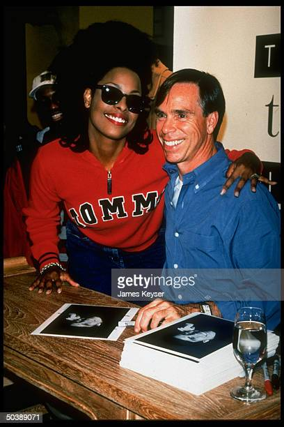 Fashion designer Tommy Hilfiger w rap singer/model Spinerella w stack of his publicity portraits at autograph party to launch his new women's...