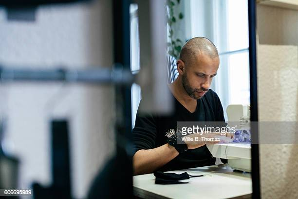 Fashion Designer using sewing machine in studio