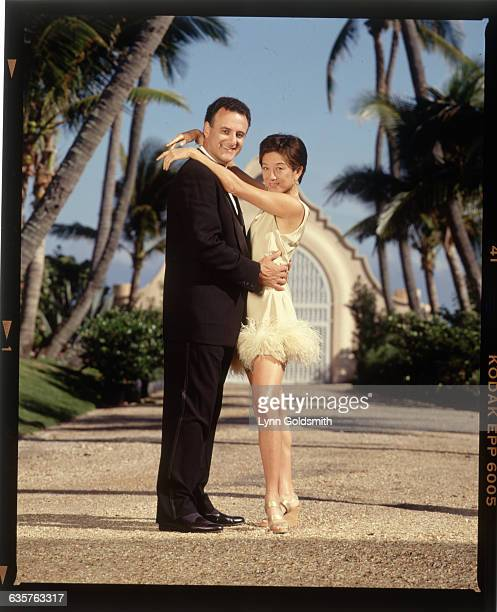 Fashion designer Vera Wang and her husband Arthur Becker dance together on driveway lined with palm trees.
