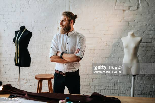fashion designer with arms crossed looking away while standing against brick wall in workshop - ファッションデザイナー ストックフォトと画像