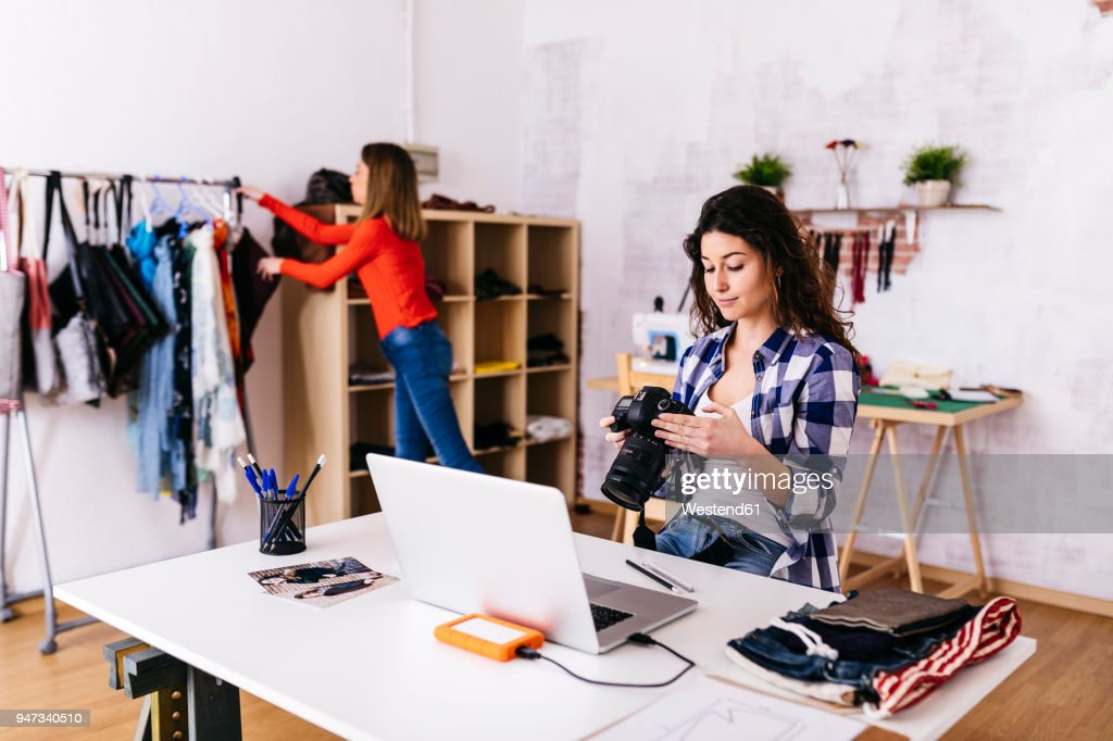 Fashion designer with camera and laptop in studio : Stock Photo