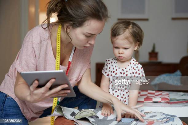 Fashion designer with digital tablet looking at fabric while standing by daughter
