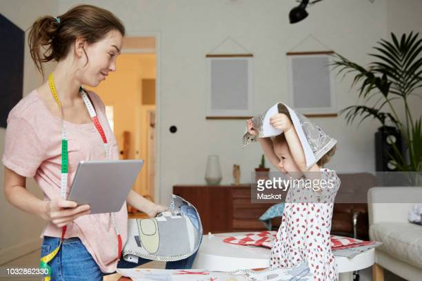 Fashion designer with digital tablet looking at playful daughter holding textile