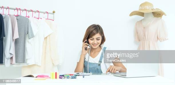 fashion designer woman working on her designs in the studio. successful fashion designer. fashion designer stylish showroom concept. designer measuring textile material - デザイナー服 ストックフォトと画像