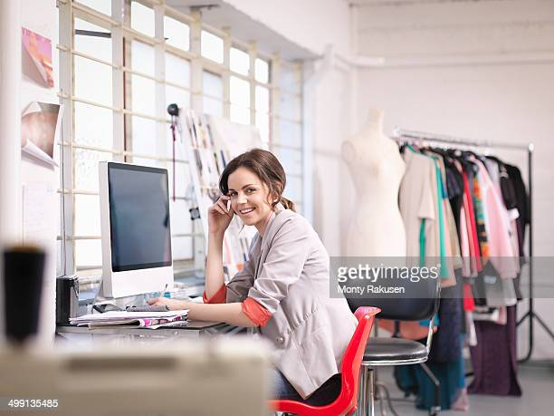Fashion designer working at computer in fashion design studio, portrait