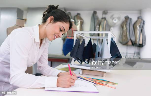 Fashion designer working at her atelier drawing sketches