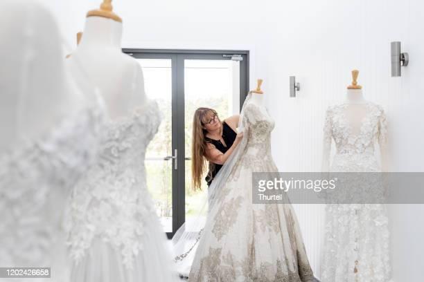 マネキンのクチュールブライダルガウンに取り組むファッションデザイナー - 裁縫道具 ストックフォトと画像
