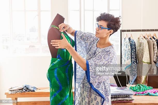 Fashion designer working on dress on dummy .