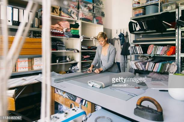 fashion designer working on template in studio - fashion industry stock pictures, royalty-free photos & images
