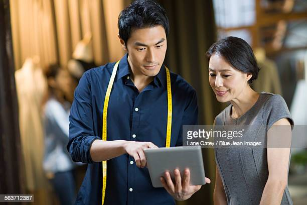 Fashion designers and customer looking at digital tablet