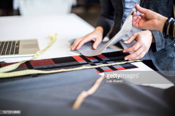 fashion designers discussing over fabric swatch at workbench - textile industry stock pictures, royalty-free photos & images