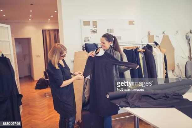 Fashion designers. Female fashion designer with customer in fashion design studio