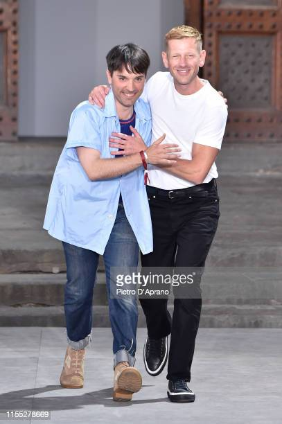 Fashion designers Guillaume Meilland and Paul Andrew acknowledge the audience at the end of the Salvatore Ferragamo fashion show in Piazza della...