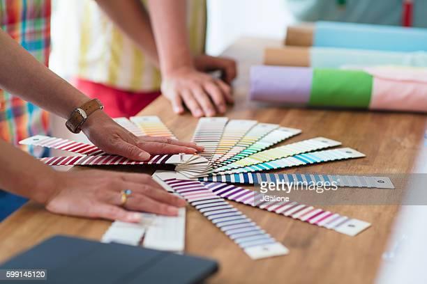 fashion designers looking at fabric samples - 裁縫道具 ストックフォトと画像