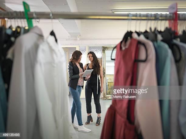 Fashion designers using digital tablet in fashion design studio