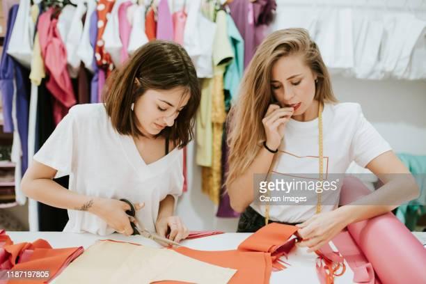 fashion designers working together in the design studio - 裁縫道具 ストックフォトと画像