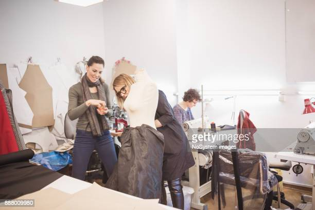 Fashion designers working together. Two famale tailors working together  on fashion model's dress in fashion design studio