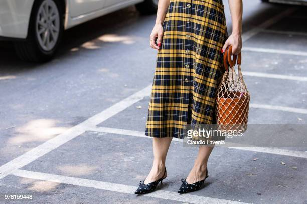 Fashion detail of Staud brown bag is seen in the streets of Milan before the Giorgio Armani show during Milan Men's Fashion Week Spring/Summer 2019...