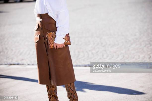 Fashion details of brown midi leather skirt snake print boots and snake print bag are seen before the Rochas show on September 26 2018 in Paris France