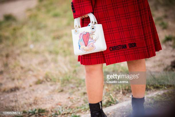 Fashion details of Dior red checked skirt and bag are seen before the Christian Dior show on September 24 2018 in Paris France