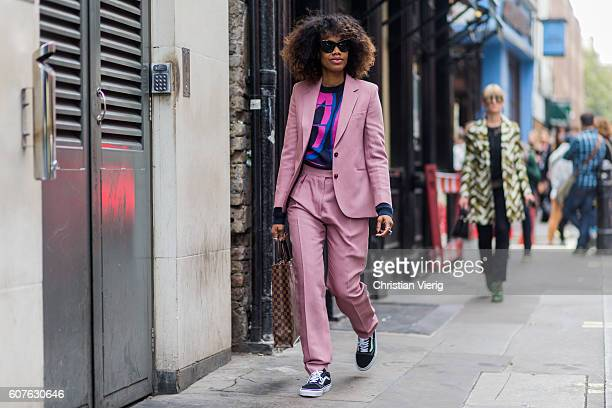 Fashion Director Instyle Germany Jan-Michael Quammie wearing a pink suit, Louis Vuitton bag and Vans outside Mary Katrantzou during London Fashion...