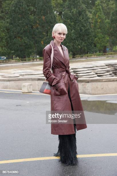 Fashion director of Lu2019Officiel Ukraine Olga Yanul wears a Nebo coat and earrings Frolov trousers and a Volon bag day 3 of Paris Womens Fashion...