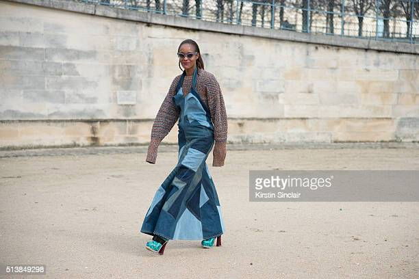Fashion editor at Garage magazine Michelle Elie wears Junya Watanabe dress and Stevan sweater and Miu Miu sunglasses and shoes on day 4 during Paris...