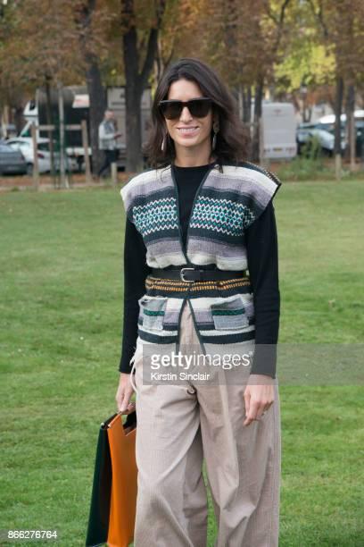 Fashion editor for L'Official fashion and fashion blogger Deborah Reyner Sebag wears a Delpozo bag Uniqlo trousers Givenchy sunglasses vintage top...