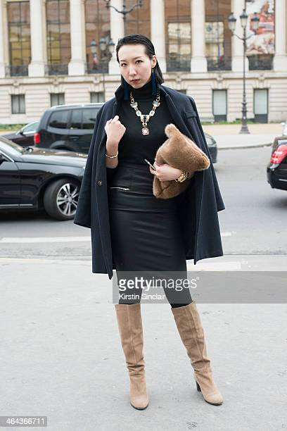 Fashion editor for Sinacom Yumeng Cheung wears vintage jewellery Defuse boots Zara skirt Burberry sweater jacket from a Korean boutique and the bag...