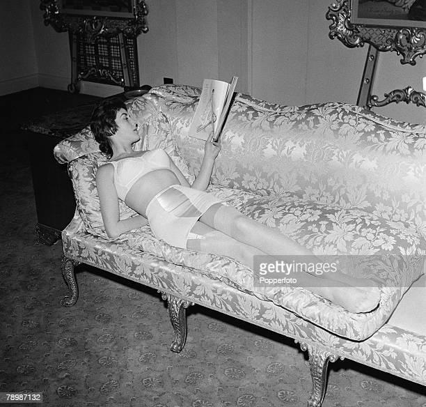 Fashion England A model relaxes on a sofa reading a book wearing a light coloured corset