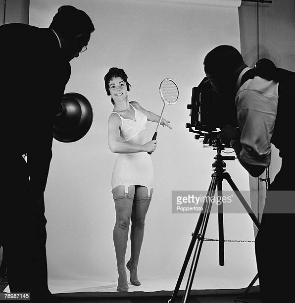 Fashion England A model wearing a light coloured corset with bra holds a badminton racket while the photographer views the scene through his camera