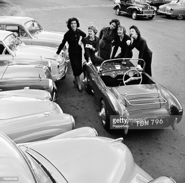 Fashion England Circa 1950's Five young women relax by various motor cars of the era