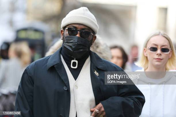 Fashion enthusiast wearing a fashionable face mask attends day one of the London Fashion Week - Autumn/Winter collection fashion show at The Strand...