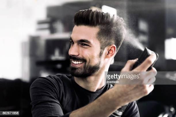 guy de mode à l'aide de laque - coiffure homme photos et images de collection