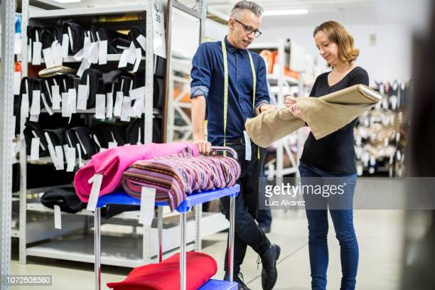 fashion industry workers discussing over the fabric - cream colored shoe stock pictures, royalty-free photos & images