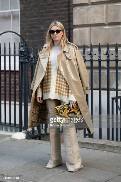 Fashion influencer Camille Charriere wears a Burberry coat House of Dagmar sweater Mulberry trousers Dries Van Noten clutch bag Le Specs sunglasses...