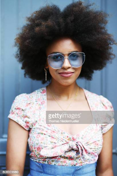 Fashion journalist Aminata Belli wearing a flower tshirt blue sunglasses and denim pants is seen during the MercedesBenz Fashion Week Berlin...