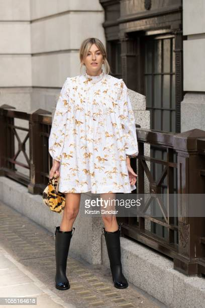 Fashion Journalist and digital influencer Camille Charriere wears a Ganni dress, Jimmy Choo boots and a Hayward House bag during London Fashion Week...