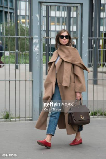 Fashion journalist Darja Barannik wears a Mulberry bag Toteme coat Ray Ban sunglasses Levi's jeans and Gucci shoes day 3 of Paris Womens Fashion Week...